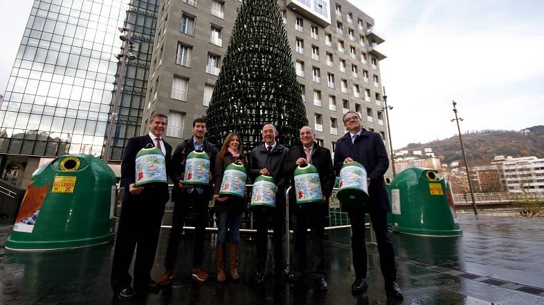 Los impulsores de la iniciativa posan junto al árbol hecho con botellas de vidrio